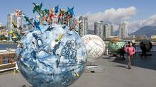 Some of the 23 one-tonne globes placed along the seawall outside Science World are seen in downtown Vancouver, Thursday, April 22, 2010. (Jonathan Hayward/THE CANADIAN PRESS)