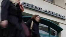 Pedestrians walk in front of a branch of French bank Crédit Agricole in Marseille Feb. 1, 2013., France's No. 3 bank announced a further $5.2-billion (U.S.) in charges on Friday as banks struggle to move on from ill-timed deals made before the 2008 financial crisis. (JEAN-PAUL PELISSIER/REUTERS)
