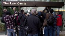 Media gather outside the British Columbia Supreme Court in Vancouver, B.C. Monday, Sept, 30, 2013. The case dealing with the 2007 Surrey murders which left six dead began Monday. (JONATHAN HAYWARD/THE CANADIAN PRESS)