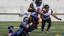 Hamilton Tiger-Cats quarterback Jeremiah Masoli, centre, attempts to shake off the tackle from Montreal Alouettes' Ameet Pall during pre-season CFL action in Hamilton, Ont., Saturday, June 14. (Aaron Lynett/THE CANADIAN PRESS)