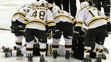 The Boston Bruins lean over fallen teammate Marc Savard after a hit in the third period of an NHL hockey game against the Pittsburgh Penguins in Pittsburgh, Sunday, March 7, 2010. Savard was taken from the ice on a stretcher. The Penguins won 2-1. (AP Photo/Keith Srakocic) (Keith Srakocic)
