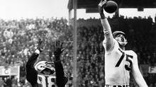 Montreal Alouettes' Hal Patterson (75) makes a spectacular one-handed pass interception at Empire Stadium in Vancouver during Grey Cup game against the Edmonton Eskimos. The ball was intended for Rollie Miles (98). At rear, is Al's Johnny Williams, No. 86. Edmonton went on to win the game 34-19. (AP)