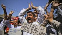 Indians in the state of Jammu shout slogans during a protest against the hike of petrol prices by nearly 11.5 per cent countrywide on Thursday, May 24, 2012. (Channi Anand/Associated Press/Channi Anand/Associated Press)