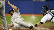 Toronto Blue Jays catcher John Buck, right, tags out Boston Red Sox's Kevin Youkilis at home plate during the first inning of a baseball game on Monday April 26, 2010, in Toronto. (FRANK GUNN/THE CANADIAN PRESS)