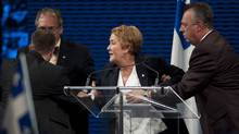 Parti Quebecois leader Pauline Marois is removed from the stage by SQ officers as she speaks to supporters in Montreal, Tuesday, September 4, 2012 following her election win (Graham Hughes/The Canadian Press)