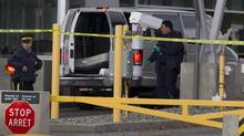 Police investigate a van at the scene of a shooting at the Canadian border crossing in Surrey, B.C., on Oct. 16, 2012. (JONATHAN HAYWARD/THE CANADIAN PRESS)