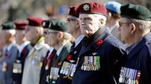 Veterans await the start of Remembrance Day ceremonies at the National War Memorial in Ottawa November 11, 2014. (CHRIS WATTIE/REUTERS)