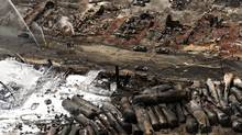 The downtown core lays in ruins as firefighters continue to water smouldering rubble Sunday, July 7, 2013, in Lac Megantic, Quebec, after a train derailment ignited tanker cars carrying crude oil. (Ryan Remiorz/THE CANADIAN PRESS)