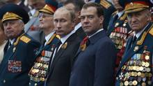 Russian President Vladimir Putin, center left, and Prime Minister Dmitry Medvedev, center right, and a group of Russian WWII veterans watch the Victory Day Parade, which commemorates the 1945 defeat of Nazi Germany on the Red Square in Moscow, Wednesday, May 9, 2012. (Alexander Zemlianichenko/Associated Press)