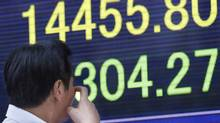 A passer-by watches the electronic stock indicator of a securities firm in Tokyo, Monday, Sept. 30, 2013 (Shizuo Kambayashi/The Associated Press)