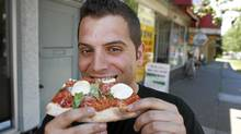 Frank Morra, owner of Ragazzi Pizza, takes a bite from a slice of his authentic Italian thin crust pizza in Vancouver on July 8, 2010. (Jeff Vinnick/Jeff Vinnick/The Globe and Mail)
