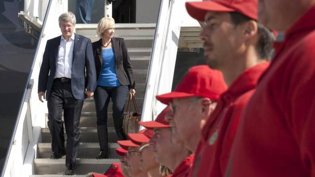 Prime Minister Stephen Harper and his wife, Laureen, are greeted by members of the Canadian Rangers as they arrive in Whitehorse on Monday for the first day of their tour of the North. (Adrian Wyld/THE CANADIAN PRESS)
