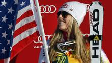 Lindsey Vonn, of the United States, celebrates while holding an American flag on the podium following her victory in the women's World Cup Super-G ski race event in Lake Louise, Alta., Sunday, Dec. 4, 2011.THE CANADIAN PRESS/Jeff McIntosh (Jeff McIntosh/CP)