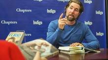 'What's going on there is very dark,' Toronto Blue Jays pitcher R.A. Dickey says of the sex trade in Mumbai. He's shown signing copies of his book, Wherever I Wind Up: My Quest for Truth, Authenticity and the Perfect Knuckleball, at a Toronto bookstore last month. (JENNIFER ROBERTS For The Globe and Mail)
