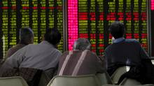 Men look at stock information at a brokerage house in Beijing, China, on Jan. 5. (KIM KYUNG-HOON/REUTERS)