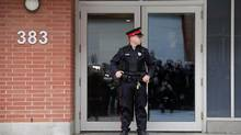 A Ottawa Police officer stand by the front front door of former Finance Minister Jim Flaherty's condo April 10, 2014 in Ottawa. (Dave Chan For The Globe and Mail)
