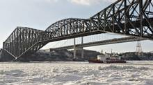 Canadian Coast Guard icebreaker Pierre-Radisson clears the ice flow under the Quebec bridge on the St-Lawrence River in front of Quebec City, Wednesday, January 8, 2014. (Jacques Boissinot/THE CANADIAN PRESS)