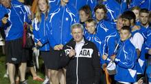 Prime Minister Stephen Harper stands with athletes as he speaks during the opening ceremonies of the Canada games Friday, August 2, 2013 in Sherbrooke, Quebec. Harper and a host of dignitaries welcomed athletes from across the country earning loud cheers, while a group of acrobats earned gasps from the crowd for their daring tricks. (JACQUES BOISSINOT/THE CANADIAN PRESS)