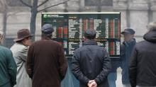 People stop and look at stock market in Milan, Italy. (Antonio Calanni/AP)