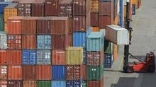 """File photo of containers being loaded at a terminal of the """"Hamburger Hafen und Logistik AG"""" (HHLA) in the harbour of Hamburg, northern Germany. (Fabian Bimmer/AP)"""