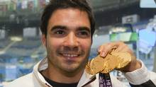 Canada's Alexandre Despatie holds up his three gold medals for diving Tuesday, October 12, 2010 at the 2010 Commonwealth Games in New Delhi, India. Despatie qualified for two events at the 2012 London Olympics this week. THE CANADIAN PRESS/Ryan Remiorz (Ryan Remiorz/CP)