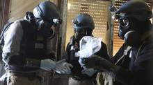 A U.N. chemical weapons expert, wearing a gas mask, holds a plastic bag containing samples from one of the sites of an alleged chemical weapons attack in the Ain Tarma neighbourhood of Damascus August 29, 2013. (STRINGER/REUTERS)
