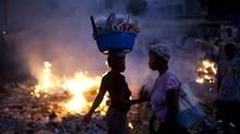 Women walk past burning garbage in downtown Port-au-Prince, Haiti. (AP)