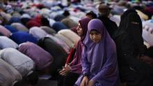 Egyptian women sit in Tahrir Square during prayer time in Cairo on June 25, 2012. (Bernat Armangue/The Associated Press)