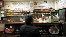 A man orders smoked meat to go from 15 year veteran Pierre (on right) at Schwartz's deli on St. Laurent in Montreal, Feb. 5, 2012. (CHRISTINNE MUSCHI/REUTERS/CHRISTINNE MUSCHI/REUTERS)