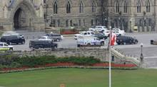 Police vehicles sit at the entrance of Centre Block on Parliament Hil, shot through windows of a locked down building across the street, on October 22, 2014. (Kevin Wiltshire/The Canadian Press)