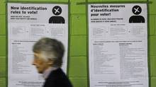A woman passes by a sign in both French and English informing the public on identification needed to vote on election day in Montreal, Tuesday Oct. 14, 2008. (Graham Hughes/THE CANADIAN PRESS/Graham Hughes)