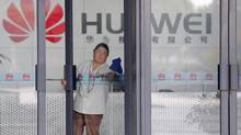 A cleaner wipes the glass door of a Huawei office in Wuhan, Hubei province October 9, 2012. (DARLEY SHEN/REUTERS)