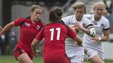 England's Natasha Hunt, center, is tackled by Canada's Emily Belchos, right, and Jessica Dovanne, left, during the final match of the Women's Rugby World Cup 2014, at Jean Bouin stadium, in Paris, Sunday, Aug. 17, 2014. (Michel Euler/The Associated Press)