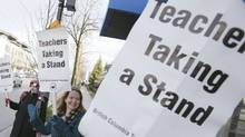 Teachers from General Brock Elementary School wave to cars outside the school and hold up signs while on strike in Vancouver, British Columbia March 5, 2012. (Ben Nelms /Reuters/Ben Nelms /Reuters)