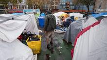 A resident stands in a tent city on a city-owned lot at 58 West Hastings St. as the city begins to clear the lot where people have been camped since July, in Vancouver, B.C., on Tuesday October 25, 2016. (DARRYL DYCK/THE GLOBE AND MAIL)