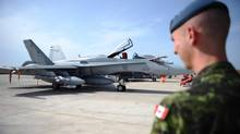 A Canadian soldier looks at a CF-18 as it at Camp Fortin in Trapani, Italy, on September 1, 2011. THE CANADIAN PRESS/Sean Kilpatrick (Sean Kilpatrick/THE CANADIAN PRESS)