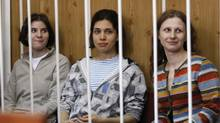 Members of female punk band Pussy Riot sit behind bars before a court hearing in Moscow. (TATYANA MAKEYEVA/REUTERS)