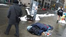 A homeless man sleeps on the southwest corner of Bay and Queen Streets. (Peter Power/The Globe and Mail)