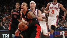 The Toronto Raptors' Jerryd Bayless, left, is fouled by the New York Knicks' Mike Bibby. (Frank Franklin II/Associated Press)