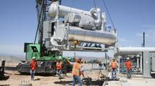 Workers move a generator into place at Raser Technologies' geothermal plant near Minersville, Utah, on Aug. 27, 2008. (Nichola Groom/Reuters)