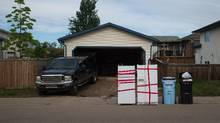 Fridges to be disposed of sit outside a home in the Wood Buffalo neighborhood of Fort McMurray, Alberta, Canada, on Friday, June 3, 2016. Residents began returning home this week and companies are resuming operations after Alberta wildfires forced the evacuation of more than 80,000 people from Fort McMurray and knocked more than 1 million barrels of production a day offline this month. (Darryl Dyck/Bloomberg)