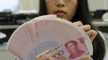 An employee counts Chinese yuan notes inside a bank in Taipei in this February 6, 2013 file photo. (REUTERS)