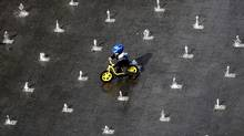 A young boy on his bike passes fountains during a sunny day in Duisburg, Germany. (Frank Augstein/Frank Augstein/Associated Press)