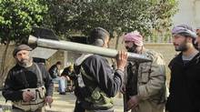 A member of the Free Syrian Army carries a missile as he talks to comrades in Idlib December 25, 2012. (Reuters)
