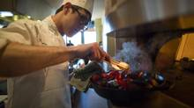 A student at the Culinary Institute of America in San Antonio, Texas roasts a few red peppers March 27, 2013. (John Lehmann/The Globe and Mail)