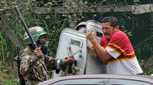 Soldiers strike a supporter of ousted Honduran President Manuel Zelaya as they disperse some 2,000 people blocking the Inter-American highway north of Tegucigalpa on July 30, 2009. (ORLANDO SIERRA/AFP/Getty Images)