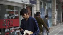 A man uses a smartphone as he walks through Connaught Place in New Delhi, India (Brent Lewin/Bloomberg)
