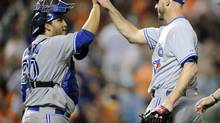 Toronto Blue Jays catcher Dioner Navarro (L) celebrates 4-0 win over the Baltimore Orioles with relief pitcher Dustin McGowan after a baseball game on Friday, June 13, 2014, in Baltimore. (Nick Wass/AP)