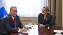 Ontario Premier Kathleen Wynne, right, is shown with Quebec Premier Philippe Couillard in her office at the Ontario Legislature on Nov. 21, 2014. (Chris Young/The Canadian Press)