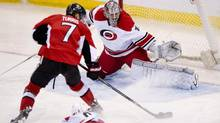 Carolina Hurricanes Andrei Loktionov slides along the ice behind Ottawa Senators Kyle Turris as he tries to score on goalie Cam Ward during second period NHL action Monday March 31, 2014 in Ottawa. (Adrian Wyld/THE CANADIAN PRESS)